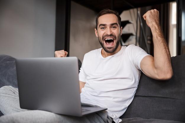 Szczęśliwy młody człowiek siedzi na kanapie, używając komputera przenośnego, obchodzi
