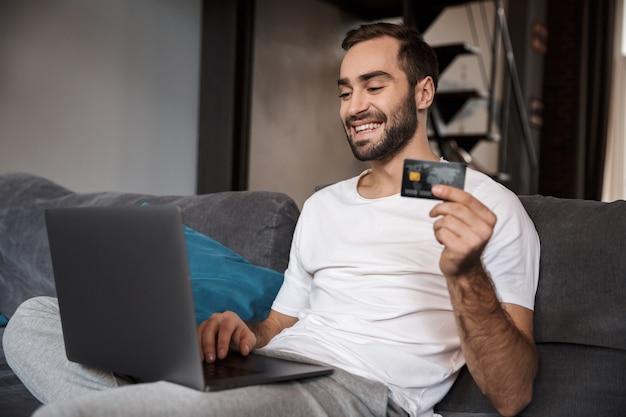 Szczęśliwy młody człowiek siedzi na kanapie, używając komputera przenośnego, świętuje, pokazując plastikową kartę kredytową