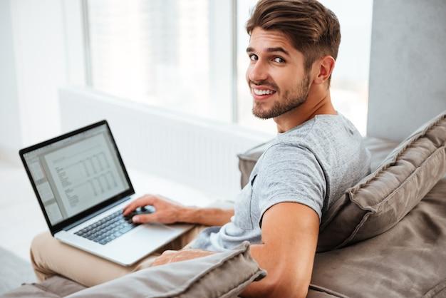 Szczęśliwy młody człowiek siedzi na kanapie w domu w t-shirt. praca na komputerze przenośnym i uśmiechnięty, patrząc na kamery.