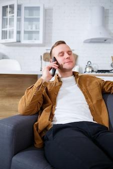 Szczęśliwy młody człowiek siedzi na kanapie w salonie przy filiżance kawy i rozmawia przez telefon.