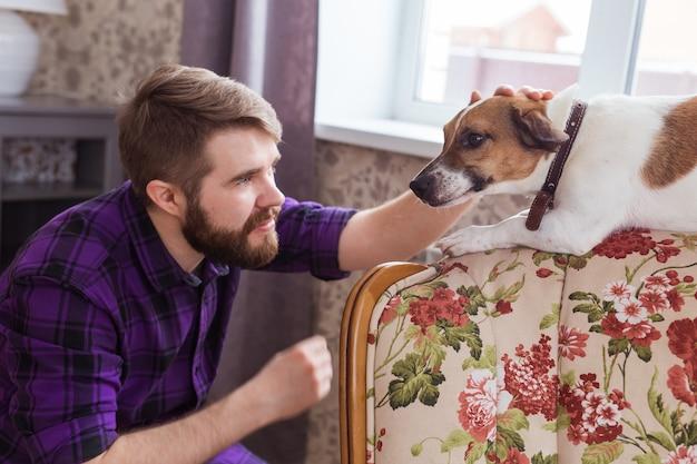 Szczęśliwy młody człowiek siedzi z psem w domu. właściciel zwierząt domowych, zwierzęta i koncepcja przyjaźni.