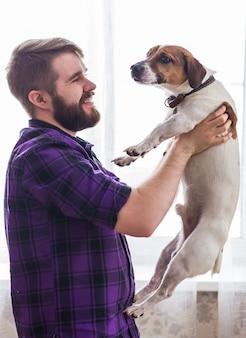 Szczęśliwy młody człowiek siedzi z psem w domu