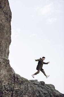 Szczęśliwy młody człowiek skacze ze skały. pojęcie sukcesu