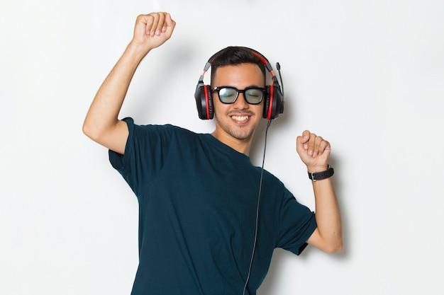 Szczęśliwy młody człowiek słucha muzyki tańczy i bawi się na białym tle