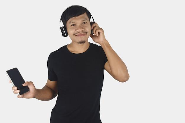 Szczęśliwy młody człowiek słuchający muzyki w słuchawkach na białym tle kopii przestrzeni