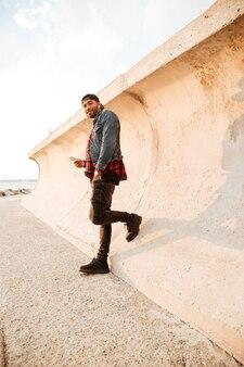 Szczęśliwy młody człowiek spaceru na plaży i rozmawiając przez telefon podczas słuchania muzyki przez słuchawki. patrząc na bok.