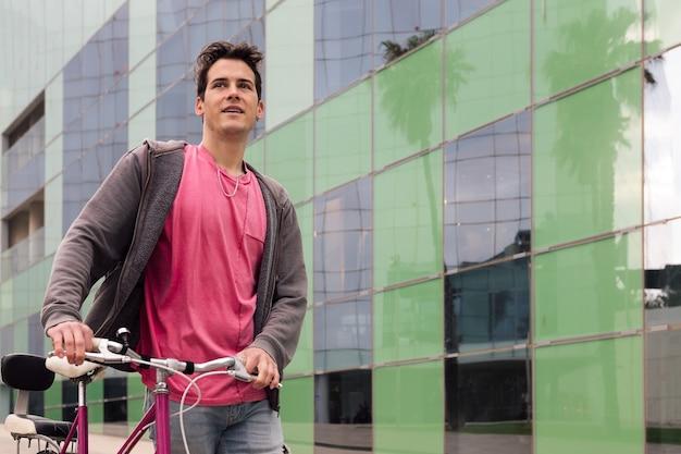 Szczęśliwy młody człowiek spacerujący po mieście z rowerem