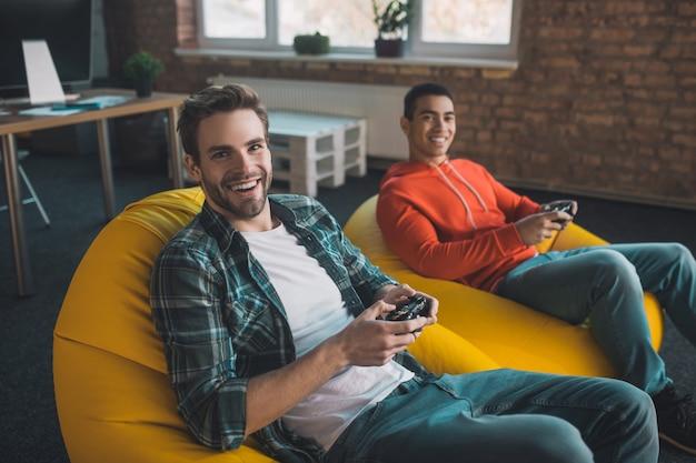 Szczęśliwy młody człowiek spędza czas z przyjacielem podczas grania w gry wideo