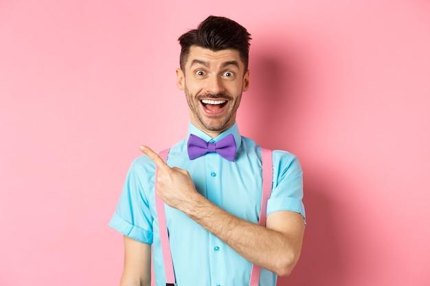 Szczęśliwy młody człowiek sprawdzający ofertę promocyjną, uśmiechnięty zdumiony i wskazujący palcem w lewo w miejsce, w pobliżu logo na różowym tle.