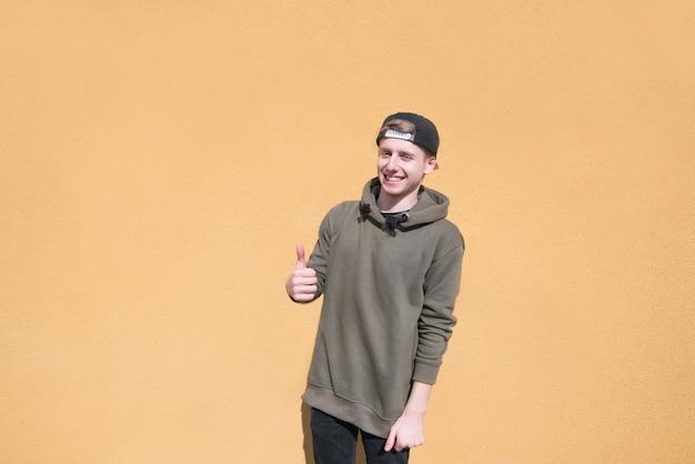 Szczęśliwy młody człowiek stoi na pomarańczowej ścianie, pokazuje kciuki do góry i uśmiecha się