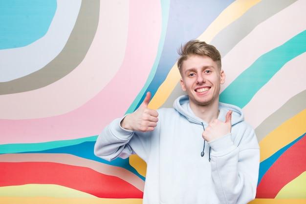 Szczęśliwy młody człowiek stoi na tle kolorowej ściany, unosi palce i uśmiecha się