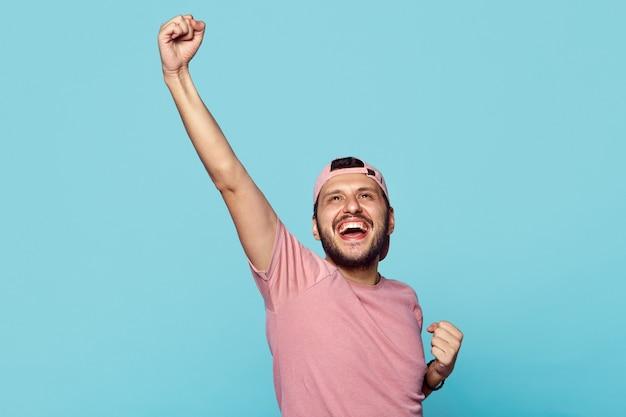 Szczęśliwy młody człowiek świętuje sukces na białym tle nad niebieską ścianą