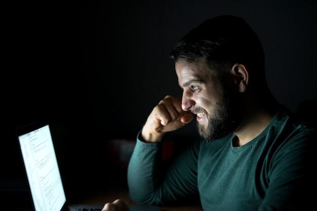 Szczęśliwy młody człowiek świętuje sukces z podniesioną pięścią przed komputerem