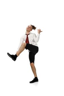 Szczęśliwy młody człowiek tańczy w zwykłych ubraniach lub garniturze, przerabiając legendarne ruchy celebrytów