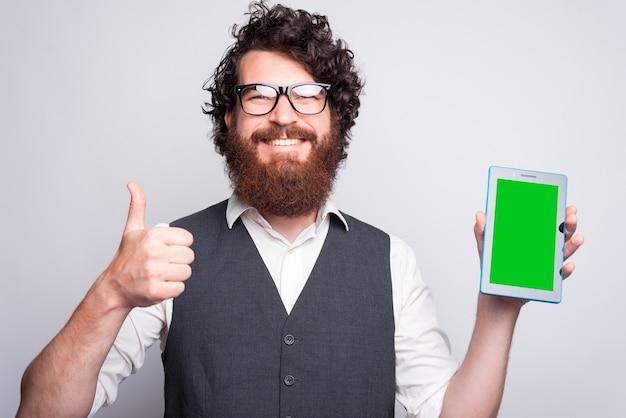 Szczęśliwy młody człowiek trzyma kciuk i podkładkę w pobliżu białej ściany