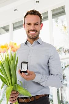 Szczęśliwy młody człowiek trzyma pierścionek zaręczynowy i bukiet kwiatów