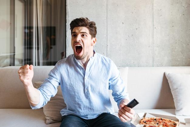 Szczęśliwy młody człowiek trzyma pilota do telewizora i świętuje