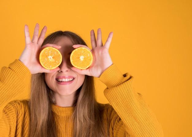 Szczęśliwy młody człowiek trzyma pomarańcze, oczy zakrywające w pomarańcze. na pastelowej żółtej ścianie