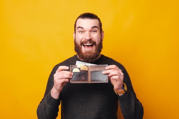 Szczęśliwy młody człowiek trzyma portfel pełen bitcoinów z uśmiechem
