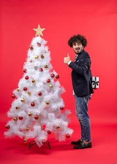 Szczęśliwy młody człowiek trzyma prezent za stojącą, robiąc ok gest w pobliżu udekorowanego białego drzewa xmas po prawej stronie czerwieni