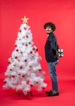 Szczęśliwy młody człowiek trzyma prezent za stojący w pobliżu zdobione białe drzewo xmas po prawej stronie czerwieni