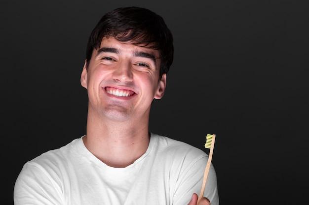 Szczęśliwy młody człowiek trzyma szczoteczkę do zębów