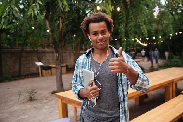 Szczęśliwy młody człowiek trzyma tablet w słuchawkach i pokazuje kciuk do góry