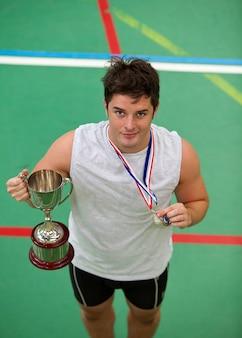 Szczęśliwy młody człowiek trzyma trofeum i medal