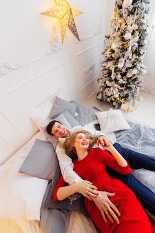 Szczęśliwy młody człowiek trzymający rękę na brzuchu ciężarnej żony leżącej na łóżku