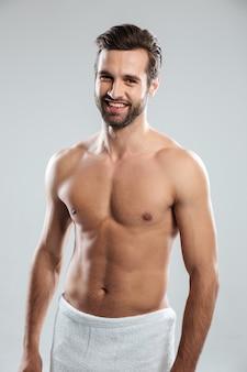 Szczęśliwy młody człowiek ubierał w ręcznikowej pozyci odizolowywającej