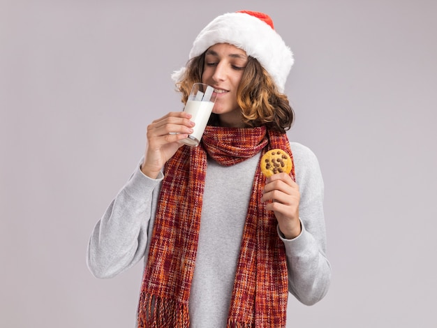 Szczęśliwy młody człowiek ubrany w boże narodzenie santa hat z ciepłym szalikiem na szyi pije mleko trzymając plik cookie
