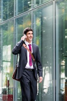 Szczęśliwy młody człowiek ubrany w garnitur, rozmawiając przez telefon komórkowy i idąc wzdłuż nowoczesnego budynku firmy