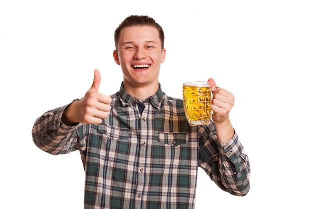 Szczęśliwy młody człowiek uśmiecha się do kamery, pokazując kciuk do góry, trzymając szklankę piwa. podekscytowany mężczyzna pozowanie przy drinku. uroczystość, browar. koncepcja wypoczynku