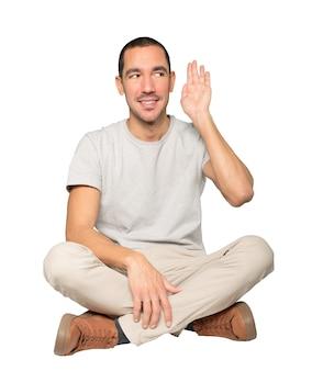 Szczęśliwy młody człowiek uśmiecha się i robi gest próbując usłyszeć coś