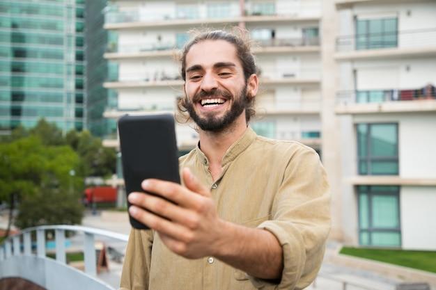 Szczęśliwy młody człowiek używa smartphone