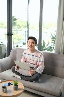 Szczęśliwy młody człowiek używa swojego laptopa do sprawdzania poczty i sprawdzania pracy online. praca w domu koncepcja.