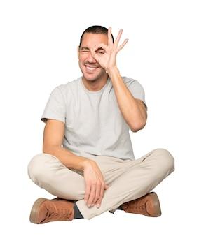 Szczęśliwy młody człowiek, używając rąk jak lornetki