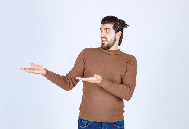 Szczęśliwy młody człowiek w brązowym swetrze stoi i pokazuje coś rękami.