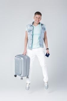 Szczęśliwy młody człowiek w dżinsowej kamizelce z walizką i skoki paszportowe