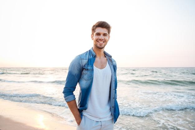 Szczęśliwy młody człowiek w dżinsowej koszuli stojący i uśmiechający się na plaży