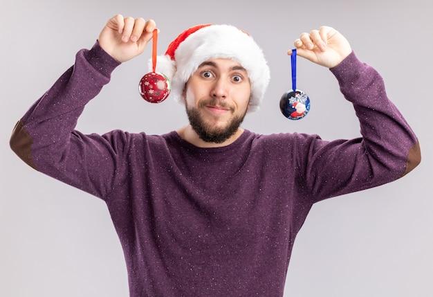 Szczęśliwy młody człowiek w fioletowy sweter i santa hat w śmiesznych okularach trzymający bombki patrząc na kamery z uśmiechem na twarzy stojącej na białym tle