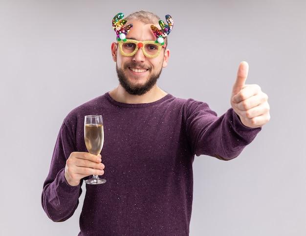 Szczęśliwy młody człowiek w fioletowym swetrze i śmiesznych okularach trzyma kieliszek szampana patrząc na kamery z uśmiechem na twarzy kucając kciuki stojąc na białym tle