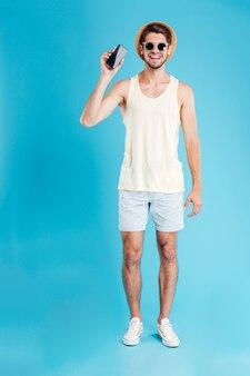 Szczęśliwy młody człowiek w kapeluszu i okularach przeciwsłonecznych, trzymając smartfon