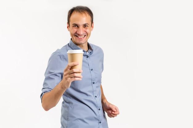 Szczęśliwy młody człowiek w koszuli trzyma w rękach filiżankę kawy, patrzy w kamerę i uśmiecha się, na białym tle na białym tle.