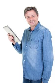 Szczęśliwy młody człowiek w niebiescy dżinsy koszula stoi i używa pastylkę nad bielem