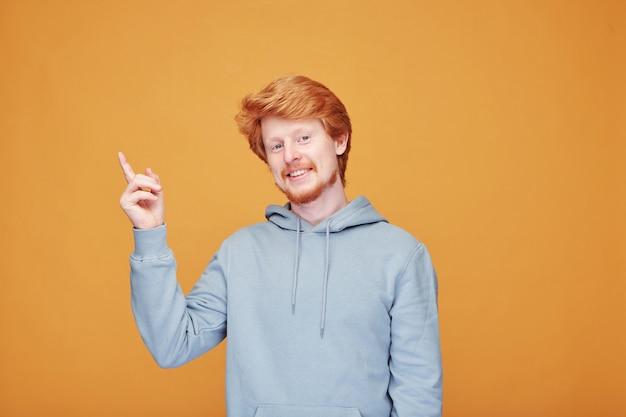 Szczęśliwy młody człowiek w niebieskiej bluzie z kapturem, wskazując w górę, pokazując coś lub wyrażając satysfakcję na żółtej ścianie