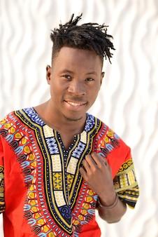 Szczęśliwy młody człowiek w nigeryjskim obywatelu odziewa na białej ścianie