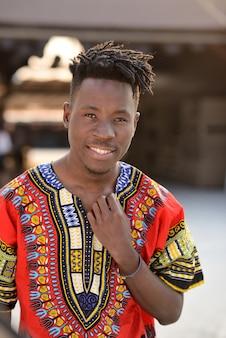Szczęśliwy młody człowiek w nigeryjskim obywatelu odziewa outdoors