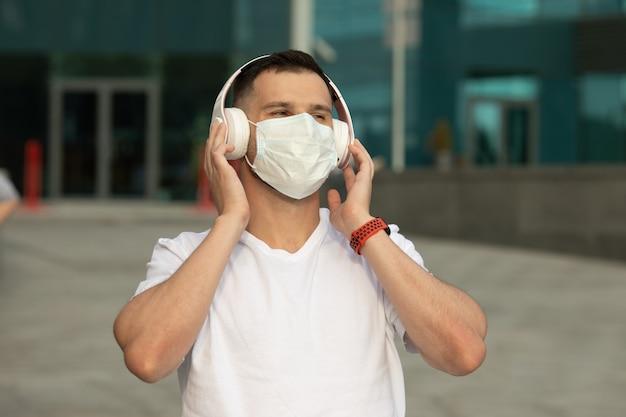 Szczęśliwy młody człowiek w ochronnej masce medycznej słucha muzyki przez bezprzewodowe słuchawki bluetooth. koronawirus covid-19.