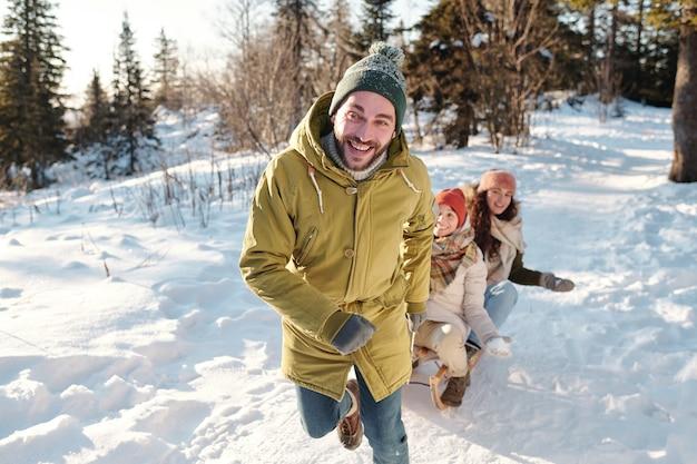 Szczęśliwy młody człowiek w odzieży zimowej biegnie drogą między zaspami, ciągnąc sanie z dwiema radosnymi dziewczynami i bawiąc się w zimowy dzień